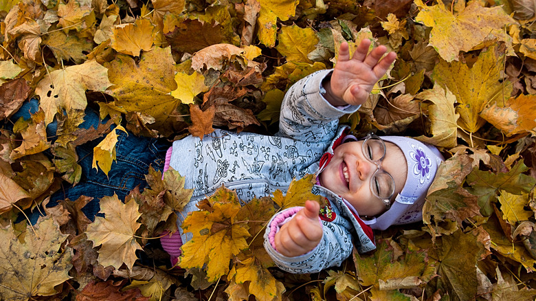 happy toddler in fall leaves