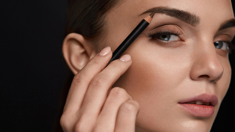 a woman filling her eyebrows