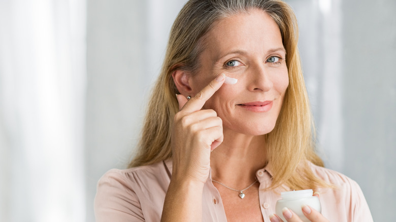 a woman applying a beauty product