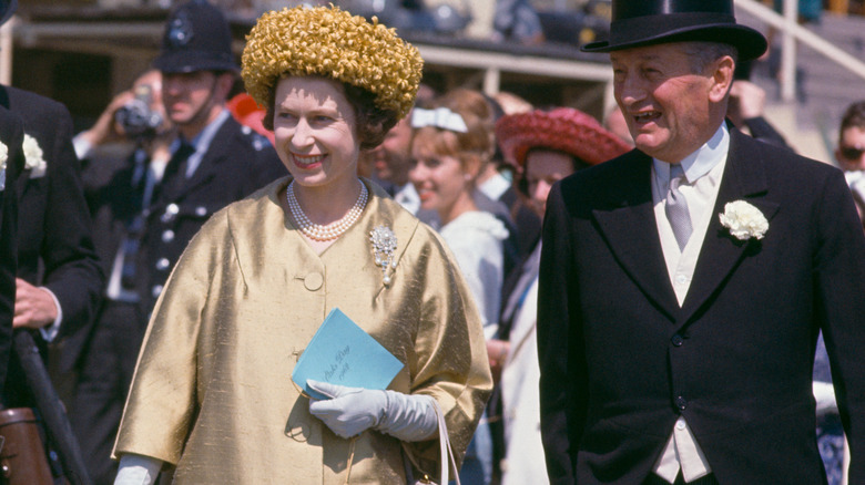 Queen Elizabeth II sporting bold fashion with gold hat and jacket