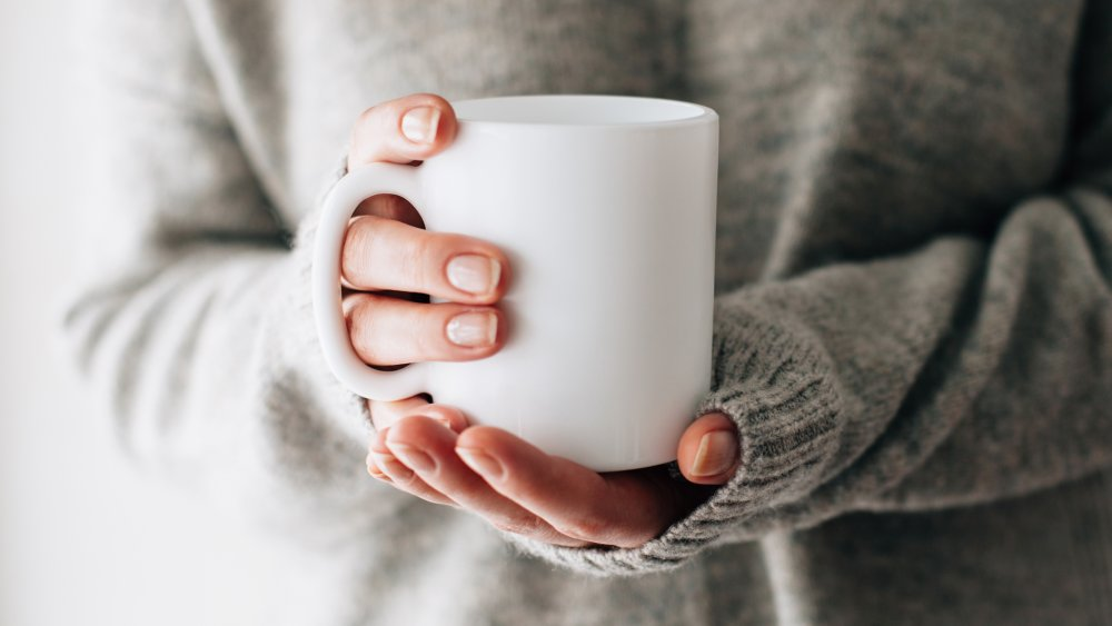 a woman holding a cup of tea