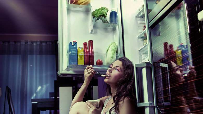 woman sitting in front of open fridge eating