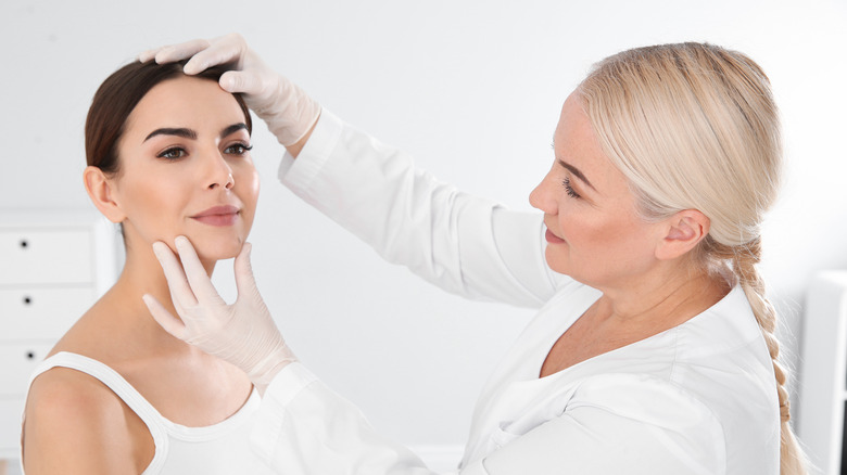 A doctor consults with a woman over her skin issues