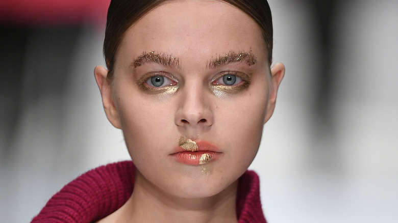 Runway model sporting glitter brows, eyes, and lips