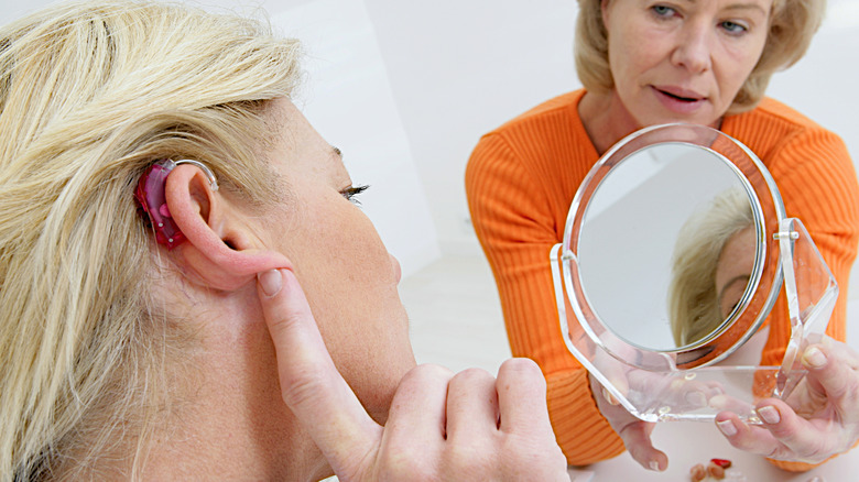 woman trying on hearing aids