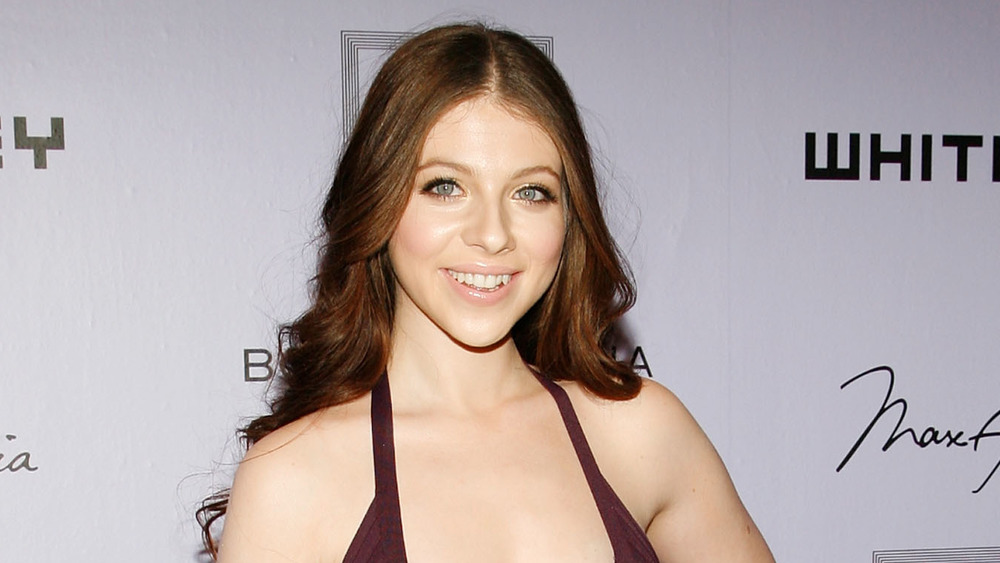 Michelle Trachtenberg on a red carpet wearing burgundy