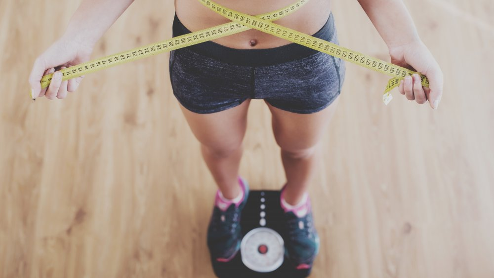 Woman on scale, measuring weight loss