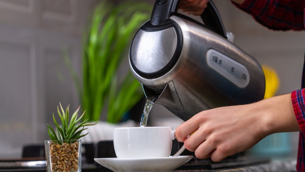 a woman pouring hot water into a mug
